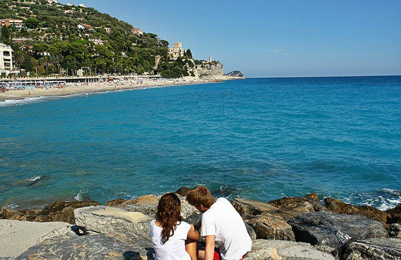 A couple is enjoying the view of Castel Gavone in Finale Ligure