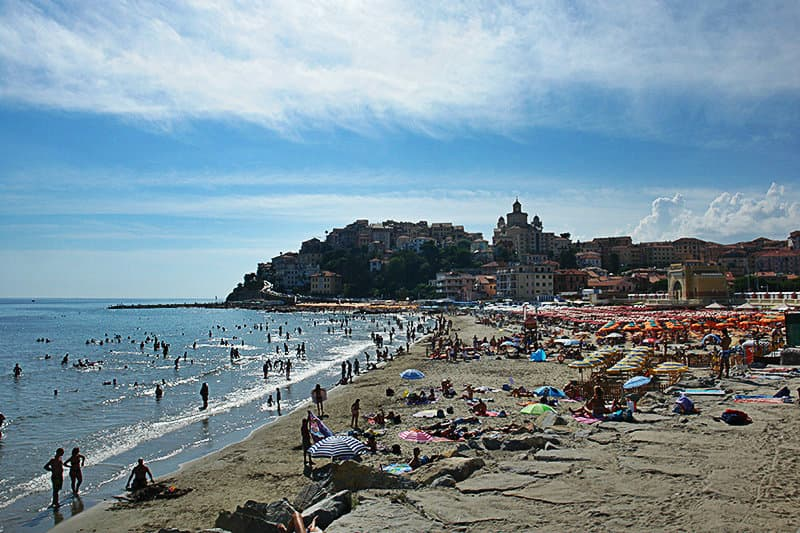 People are enjoying the sun at the sandy beach of Imperia