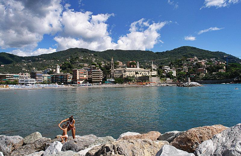 A family is playing on the rocks next to the sea in Recco
