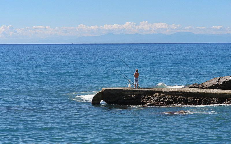 A man is fishing from stones next to the sea in Recco