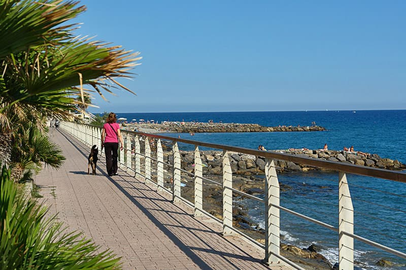 A woman walks along the coast in Riva Ligure