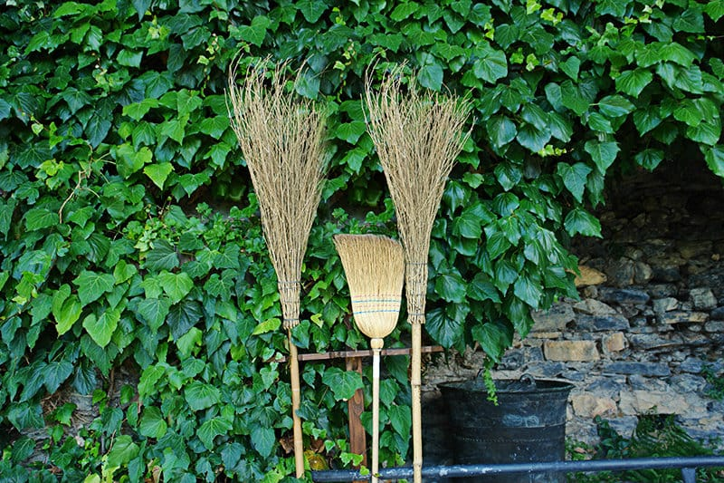Brooms are standing next to some plants in Triora, town which is often called a village of the witches