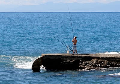 A man is fishing on the stones in Recco