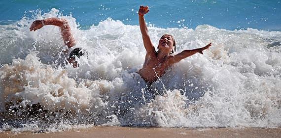 Children enjoying the waves at sandy Ligurian beaches