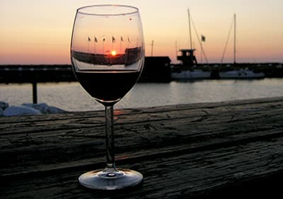 Red wine next to a port during the evening in Liguria