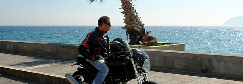 A man with a motorcycle is looking over the sea in Liguria