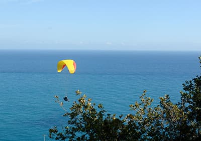 A man is paragliding over the sea in Liguria