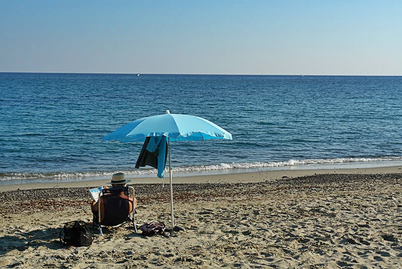 A man is enjoying the sun in the beach of Bussana