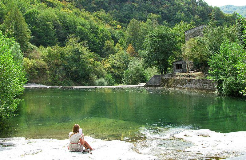 A girl reading a book at the lake of Molini di Triora