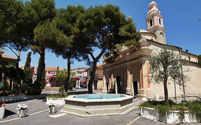 A beautiful fountain next to a church in San Lorenzo al Mare