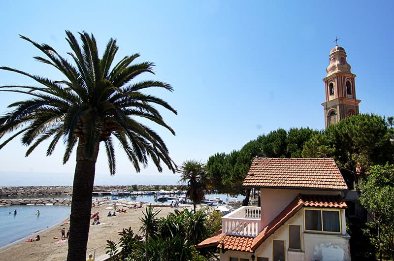 A beautiful view of Church, a palm tree and sandy beach in San Lorenzo al Mare