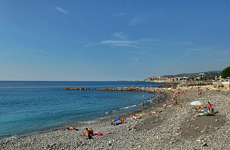 People are enjoying the sun in the sandy beach of Imperia