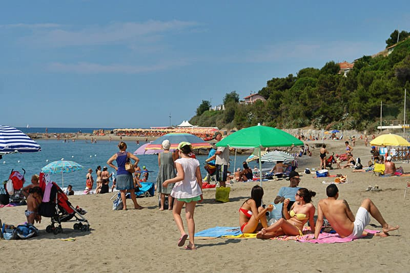 People are enjoying the sun in a sandy beach of San Lorenzo al Mare